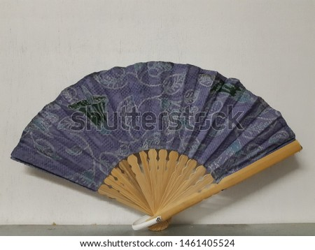 Kipas tangan or hand-held fan with pattern fabric material and wood material that can be used manually to air conditioning on white background