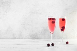 Kir Royal Champagne Cocktail on white, copy space. Flute glasses with berry sparkling champagne drink for celebrating or chilling.