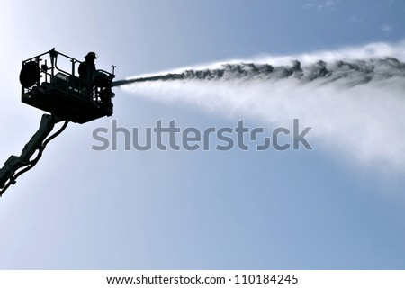 KIRYAT MALAKI, ISRAEL - DECEMBER 2: Silhouette of firefighter on a ladder spray water from a hose during an exercise on December 2 2009 in Kiryat Malaki, Israel.