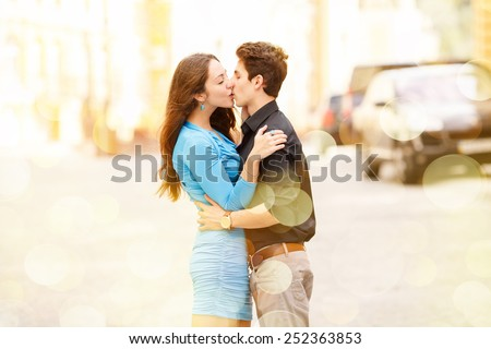 Kiss of two lovers in the city. Walking through the city. Love between two people. Honeymoon. Love story. Young happy couple in the city. Young man and beautiful woman on street. Spend their holidays.