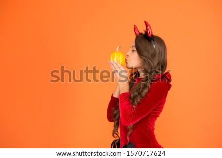 Kiss spell. Small girl kiss pumpkin orange background. Little child wear red devil horns for holiday celebration. Halloween celebration. Holiday celebration. Autumn celebration, copy space.