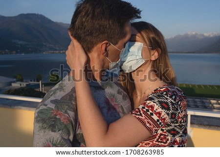 Kiss with medical protective mask on face for fear of virus infection