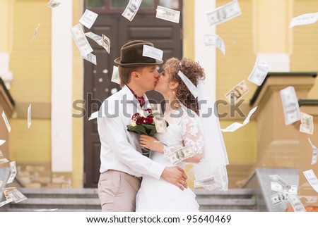 Kissing bride and groom under a rain of money