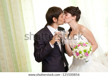 kissing bride and groom with champagne