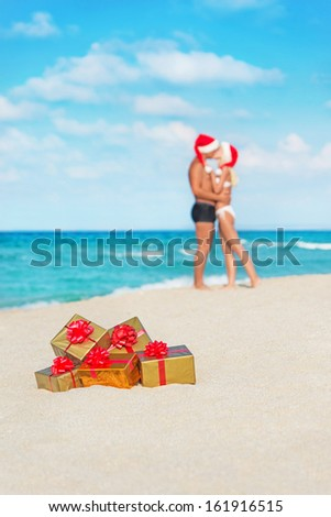 Kissing couple in santa hats at sea sand beach with christmas packed  golden gifts