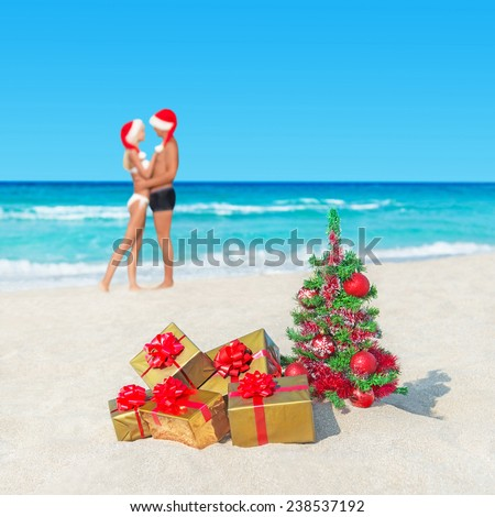 Kissing couple in santa hats at tropical  beach with christmas tree and packed golden gifts - New Years vacation in hot countries concept