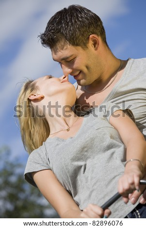 kissing couple on a swing outdoor