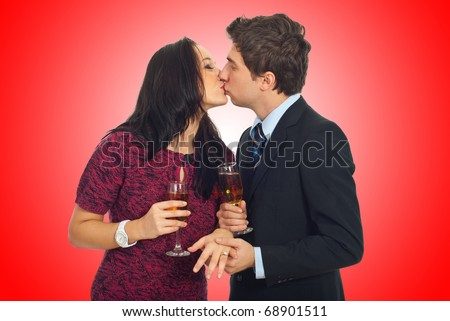Kissing couple on Valentine\'s  day ,man holding her hand with wedding ring and toasting with champagne on red background