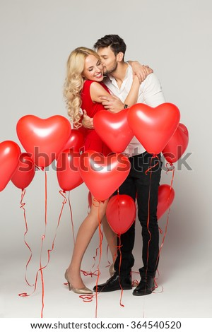 Kissing couple posing on grey background with balloons heart. Valentine\'s day.