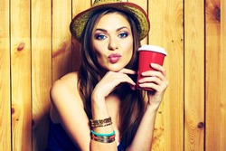 Kissing Hipster Girl Holding Coffee Cup. Yellow hat.Female  model with long hair. Beauty Face Portrait against wooden background.