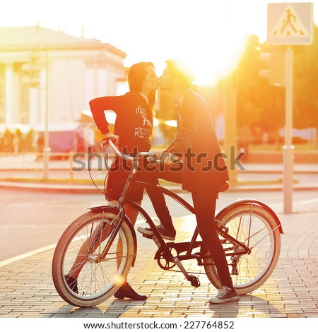 Kissing romantic couple in love Sunset Boy and girl standing near a vintage bike in urban scene