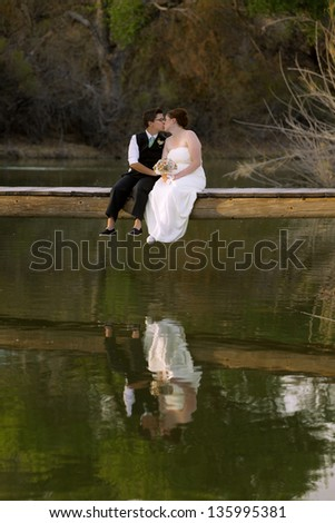 Kissing same sex newlywed on dock above lagoon