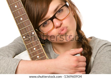 Kissy Face Musician - This is a cute young woman wearing glasses and holding a guitar making a kissy face at the camera. Shot on a white background.
