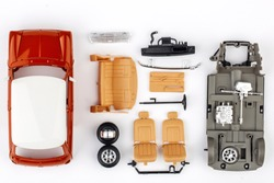 kit for assembling gray plastic car model on white background
