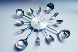 Kitchen abstract clock witch spoon and fork. Dramatic light used