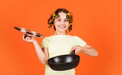 Kitchen accessories. Culinary and house duties. Stereotype housewife style. Small girl with curlers in hair. Pin up style. Girl hold Frying Pan. Little kid hold pan cooking meal. Shop home utensils