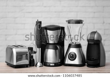 Kitchen appliances on table against brick wall background. Interior element #1106037485