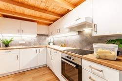 Kitchen at home with concrete texture on wall, white cabinets, regular appliances and wooden work top, floor and ceiling. Kitchen is decorated with flowers and illuminated with led lights.