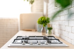 Kitchen at modern house with white interior design. Selective focus on gas stove appliance and countertop surface with blurred kitchenware supplies near green plants