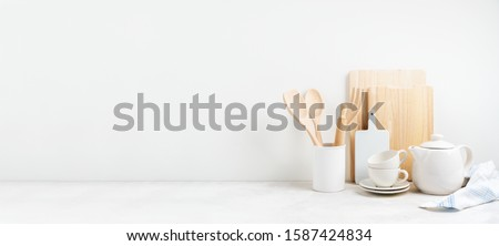 Kitchen background for mockup with teapot, cups,  rolling pin, bowls for cooking and baking utensils on the table on white background. Blank space for a text, home kitchen decor concept. Wide banner. Stockfoto ©