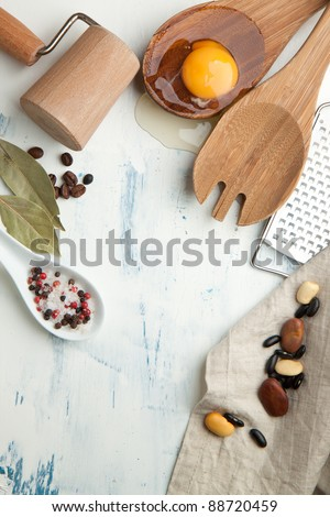 Kitchen background with kitchen utensil, broken egg, salt and pepper on white wooden table