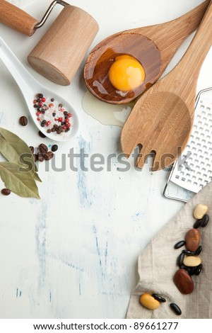 Kitchen background with kitchen utensil, broken egg, salt and pepper on white wooden table