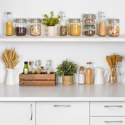 Kitchen bench shelves with various food ingredients on white background