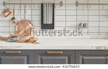 Kitchen brass utensils, chef accessories. Hanging copper kitchen with white tiles wall