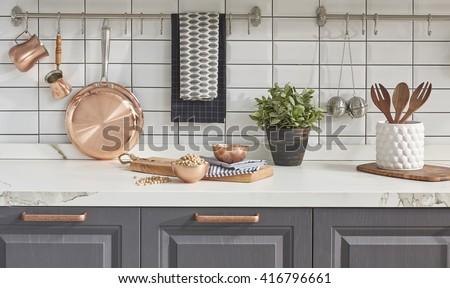Kitchen brass utensils, chef accessories. Hanging copper kitchen with white tiles wall