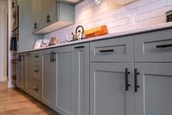 Kitchen cabinets with white countertop black handles and tile backsplash