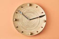 Kitchen clock made of nuts, fork and knife isolated on beige background, conceptual photography for healthy food blog