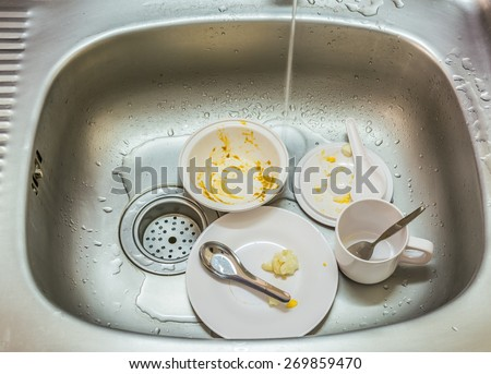 Kitchen conceptual image. Dirty sink with many dirty dishes and kitchenware.