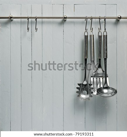 Kitchen cooking utensils on steel rack; steel spatulas etc against rustic wooden wall; good copy-space