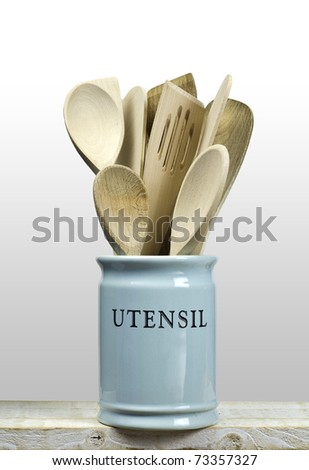 Kitchen cooking utensils; wooden spatulas etc in china storage pot; isolated on wooden shelf; background is graduated to white at top, allowing easy extension
