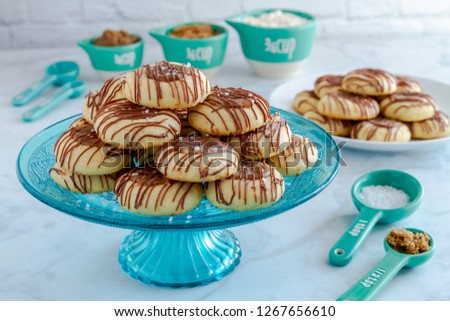 Kitchen counter with salted caramel thumbprint cookies drizzled with milk chocolate sitting on blue glass pastry stand and additional cookies on white plate surrounded by ingredients in blue utensils
