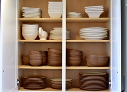 Kitchen dish cabinet neatly organized with family dishwater and crockery. Photo concept, home life background, organization