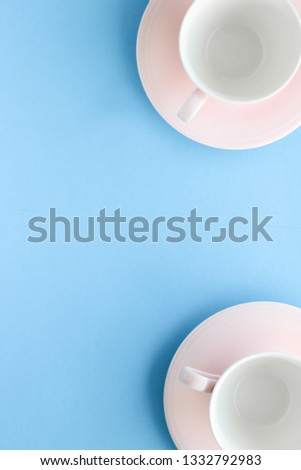 Kitchen, dishware and drinks concept - Empty cup and saucer on blue background, flatlay #1332792983