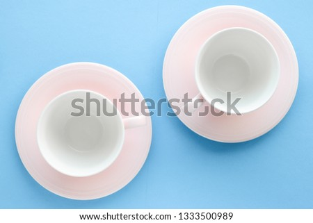 Kitchen, dishware and drinks concept - Empty cup and saucer on blue background, flatlay #1333500989