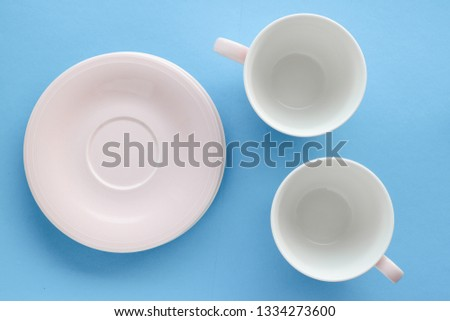 Kitchen, dishware and drinks concept - Empty cup and saucer on blue background, flatlay #1334273600