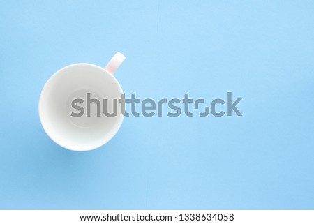 Kitchen, dishware and drinks concept - Empty cup and saucer on blue background, flatlay #1338634058