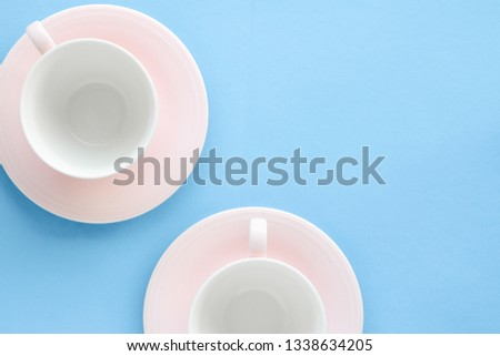 Kitchen, dishware and drinks concept - Empty cup and saucer on blue background, flatlay #1338634205