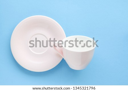 Kitchen, dishware and drinks concept - Empty cup and saucer on blue background, flatlay #1345321796