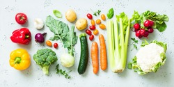 Kitchen - fresh colorful organic vegetables captured from above (top view, flat lay). Grey stone worktop as background.
