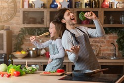 Kitchen Fun. Cheerful dad and his little daughter singing while cooking together, using spatula and broccoli as microphones