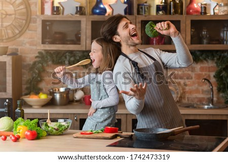 Kitchen Fun. Cheerful dad and his little daughter singing while cooking together, using spatula and broccoli as microphones stock photo