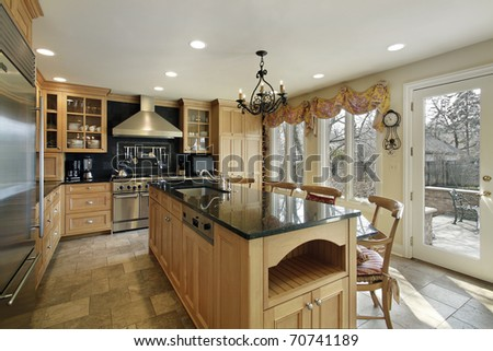 Kitchen In Luxury Home With Oak Wood Cabinetry Stock Photo