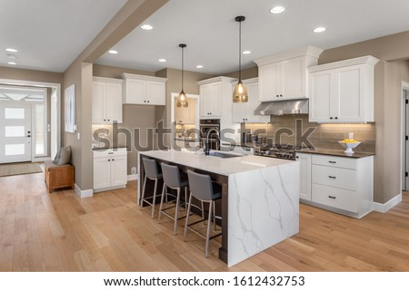 Kitchen in new luxury home with waterfall island, stainless steel appliances, pendant lights, and hardwood floors Stockfoto ©