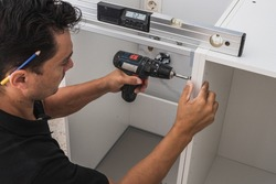 Kitchen installer using a drill to fix two pieces of a cabinet