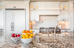 Kitchen Interior Detail in New Luxury Home with Island, Sink, Cabinets, and Bowls of Fruit