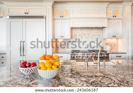 Kitchen Interior Detail in New Luxury Home with Island, Sink, Cabinets, and Bowls of Fruit #243606187